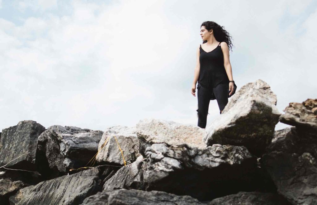 woman standing on rocky hill side